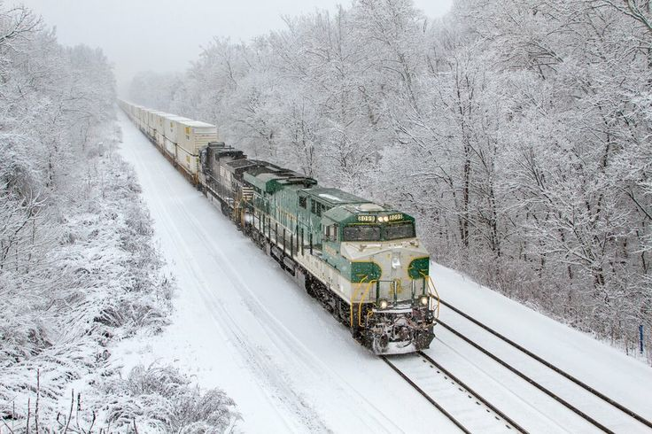 The NS Southern Railway heritage locomotive leads a double-stack intermodal train through a snowstorm in Larimer, Pa.  Photo by: Eric Johnson (yardmaster), 2016 Norfolk Southern calendar www.nscompany.store