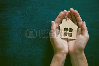 sicurezza casa mani: Mani in possesso di piccola casa di legno su sfondo lavagna. Simbolo di costruzione, la sicurezza o il concetto dolce casa