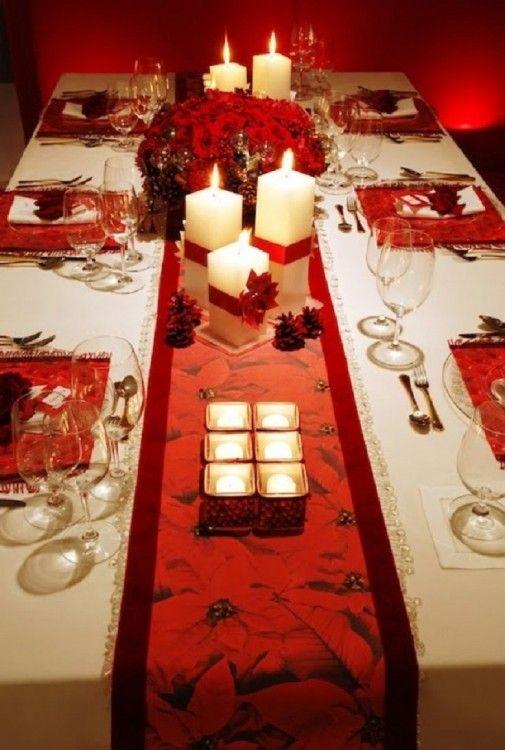 Mesa adornada con velas pequeñas y veladoras grandes cuadradas y en el centro un arreglo de flores en color rojo                                                                                                                                                                                 Más