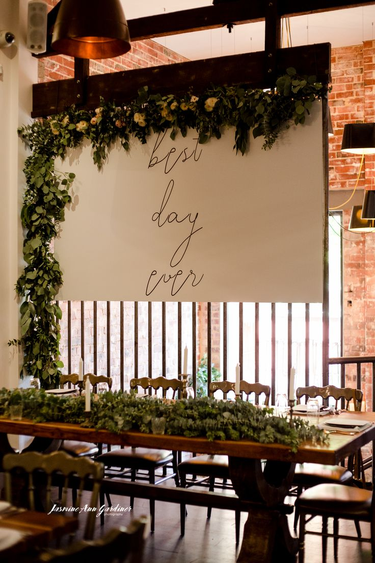 """DY.o events (aka Duo) """"Best Day Ever"""" white signage with cursive font and textured green foliage garland."""