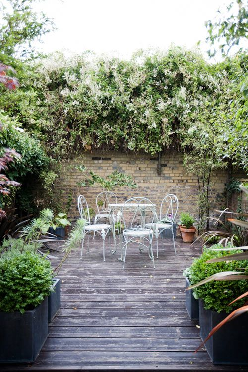 aged decking, wrought iron furniture, brick wall and overflowing climbing plants