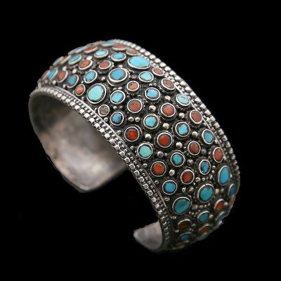 Coral Turquoise and Silver Cuff, Nepal Circa 1970. Generously drenched in turquoise and coral stones, fine example of Tibetan design. The distinctive 1970s style blends contrasting gems with ornate silver-work. It has an equally charming history, with its roots in Buddhist Kathmandu.