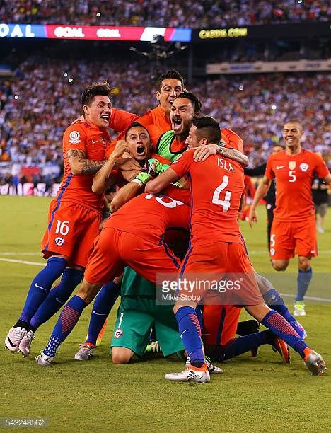 Claudio Bravo of Chile is mobbed by his teammates after defeating Argentina to win the Copa America Centenario Championship match at MetLife Stadium...