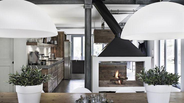 Kjøkkenet har en stor, åpen peis som virker som naturlig romdeler mot spisestuen. Den svarte skorsteinen er helt i tråd med huset industrielle stil, med synlige stålbjelker og hvitevarer i rustfritt stål. Kjøkkenet har en lokal snekker bygget av gjenbrukstre i en varm tone.