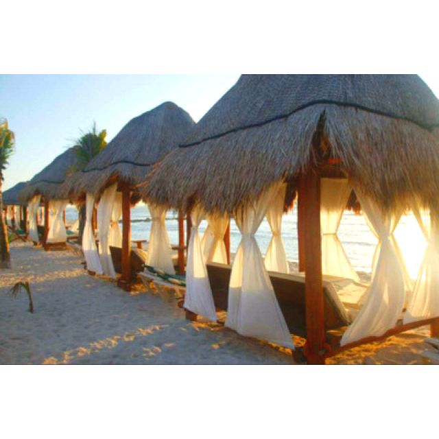Sandy beach cabana thatched roofed huts on the sea in Mexico #sunset #candlelight