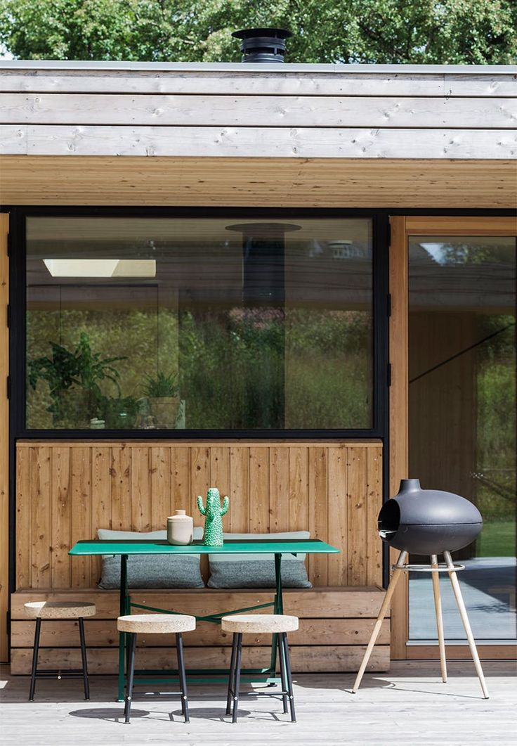 Dining area on the terrace, perfect for the bright summer evenings with a homebuilt practical bench that flares with the width of the window - a great combination together with the black stove and stools and the green table and pillows.