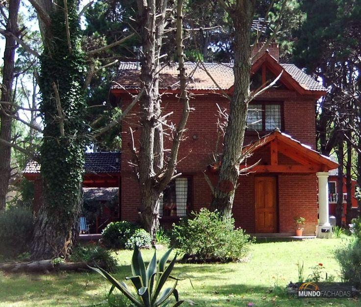 Fachada de ladrillo visto de dos pisos + detalles en madera con techo a dos aguas. Tejas color negras a juego