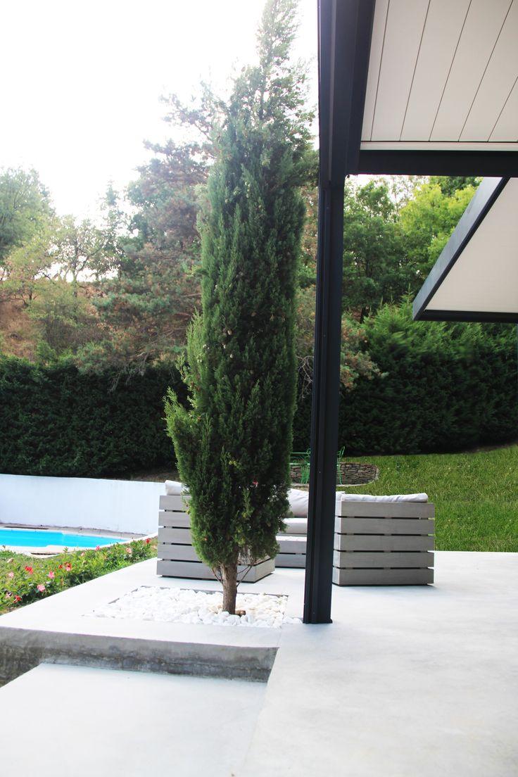 On conserve l'arbre existant en l'entourant par des galets blancs dans la nouvelle chape béton ciré