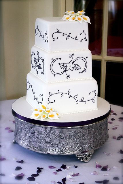 Piped Pattern Wedding Cake by Becky Colletti, ConsumedByCake on Flickr    This cake was for a gorgeous wedding yesterday at Angmering Manor, West Sussex, England    Deep aubergine piped swirls and flowers, with some sugar Callas to match the bouquet. I based the design on embroidery from the bride's Alfred Angelo wedding dress, which was also purple.