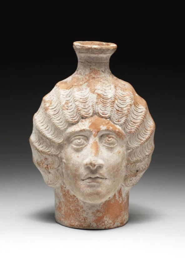 A Roman red slip ware plastic head jug  North Africa, circa 300-350 A.D.  The female head modelled in relief with wavy, centrally parted hair tied at the back in a chignon, with full lips and delicate features, the short flaring neck emerging from the top of the head, with ridged strap handle at the back, 7¾in (19.5cm) high