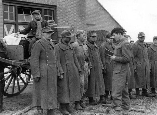 An elderly Dutch farmer on his wagon looks down on a line of German POWs being interrogated by a Lieutenant of the 1st Polish Armoured Division after Polish troops captured the Dutch towns of Alphen and Gilze en Rijen after the Battle of Tilburg and were moving on to Breda. North Brabant, Netherlands. 27 October 1944.
