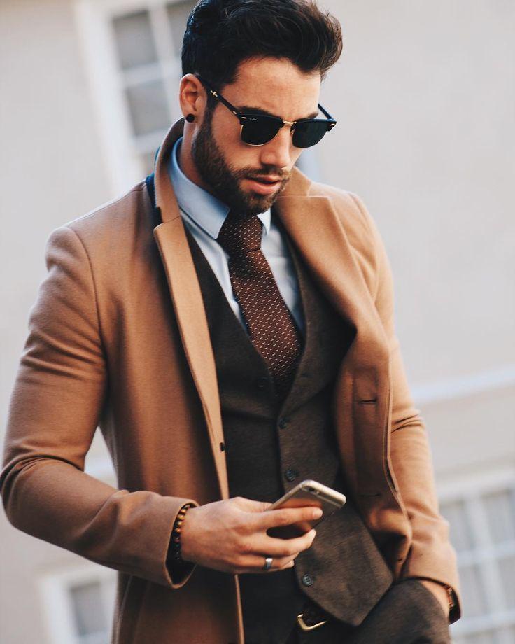 Shop this look on Lookastic:  https://lookastic.com/men/looks/overcoat-waistcoat-dress-shirt/15027  — Black Sunglasses  — Light Blue Dress Shirt  — Dark Brown Polka Dot Tie  — Dark Brown Wool Waistcoat  — Camel Overcoat  — Brown Bracelet  — Dark Brown Leather Belt  — Dark Brown Wool Dress Pants