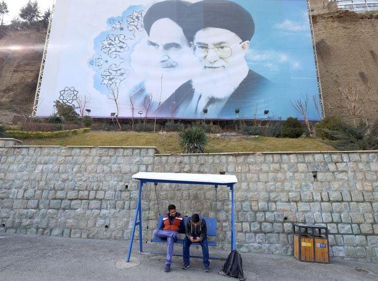 Iranian youths sit under a large picture of Iran's late leader Ayatollah Ruhollah Khomeini (L), and Iran's Supreme Leader Ayatollah Ali Khamenei at a park in Tehran, Iran, January 17, 2016. REUTERS/Raheb Homavandi/TIMA