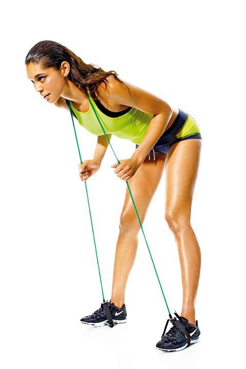BOOTY BOOST  Trabajas: glúteos, espalda baja, femorales.  Mete los pies a los mangos de la liga y párate con las piernas abiertas al ancho de las caderas. Pasa la banda detrás del cuello y sostenla con las manos a la altura del pecho, codos doblados. Lleva las caderas hacia atrás y lentamente inclina el torso hacia delante, manteniendo la espalda recta y las rodillas ligeramente flexionadas (como en la foto). Regresa a la postura inicial y repite.