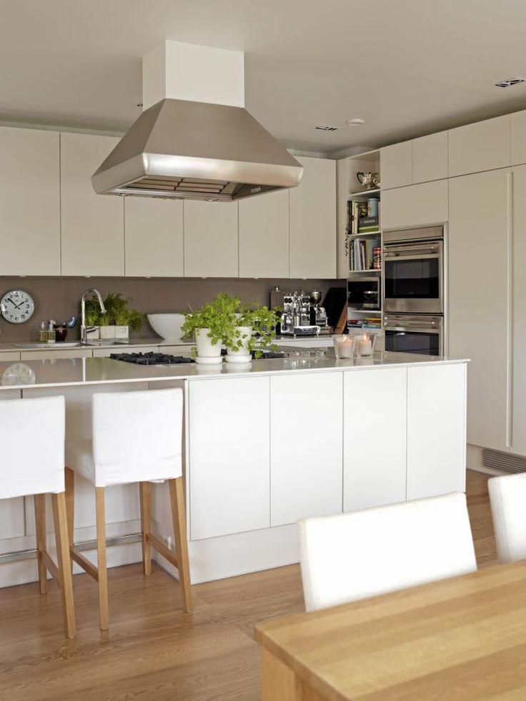 Kjøkkeninnredningen er i helhvitt med store, rene flater. Barstolene ved kjøkkenøya har hvite trekk, og trebein som matcher gulvet. Kjøkkenvifta og hvitevarene er i stål. I hjørnet er det også gjort plass til en åpen hylle med kokebøker som gjør matlagingen enklere.