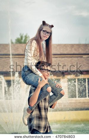 Sweethearts teenagers. Girlfriend and boyfriend together. They wear glasses. Warm toning. The boy put the girl on his shoulders. Piggyback. First love. He falls in love. Date.