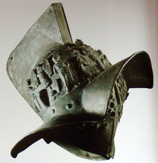 The Hoplomachus gladiator helmet. The Hoplomachus is often confused with the thraex, and indeed they have many pieces of equipment in common. The word is from the Greek, meaning simply 'armed fighter'. They both had the distinctive forward-curving crested visored helmet, though that of the hoplomachus did not appear to have the griffin's head on its crest. Both had the same high greaves, and padded leg wrappings, fasciae.