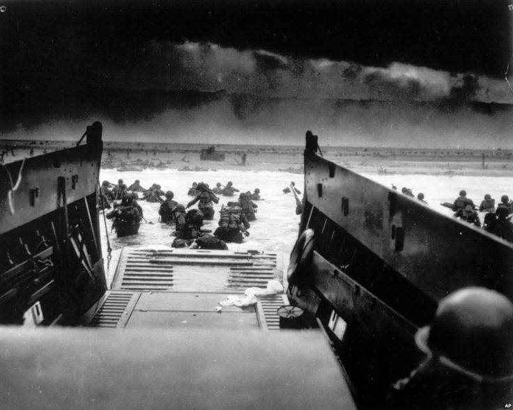 While under heavy machine gun fire from the German coastal defense forces, American soldiers maneuver off the ramp of a U.S. Coast Guard landing craft during the Allied landing operations at Normandy, France,June 6, 1944.