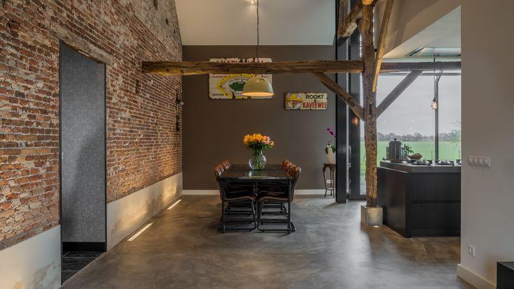 Een comfortabele eethoek met grote zwarte tafel en stoelen. Het houten spant is boven de tafel langs verbonden met de oude metselwerk muur.