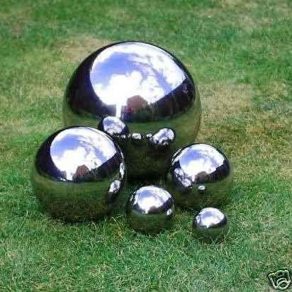 Haz esferas reflectoras para tu patio pintándolas con pintura de efecto espejo. Tu jardín se verá más grande