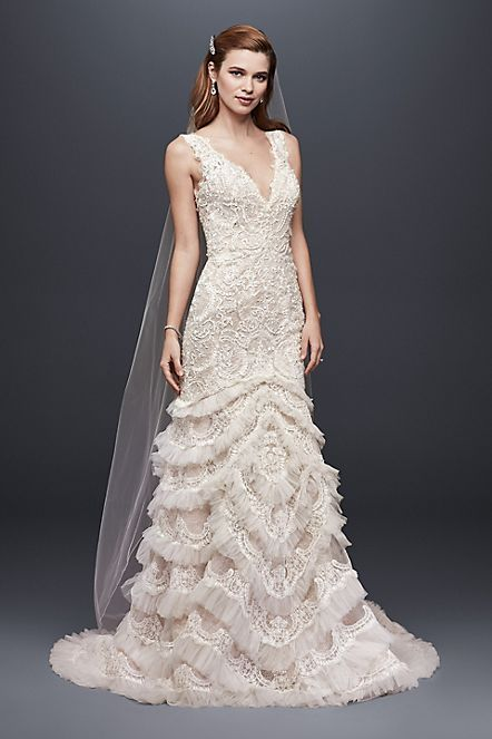 You'll feel utterly captivating in this dramatic, plunging-neckline wedding gown. The scallop-edged beaded lace bodice leads to a fit-and-flare trumpet skirt, edged in layers of tulle ruffles. The lo