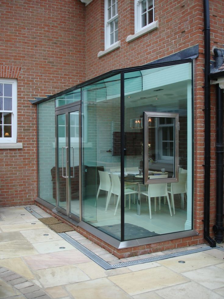 Bespoke architectural glazing is used to create a contemporary glass box extension on a traditional home in London along with an additional glass bridge and balustrading.