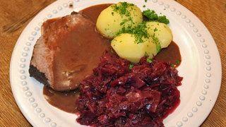 Eine Scheibe Rinderschmorbraten ist mit Sauce, Rotkohl und Petersilienkartoffeln auf einem Teller angerichtet | Bildquelle: WDR/ Moviepool Megaherz