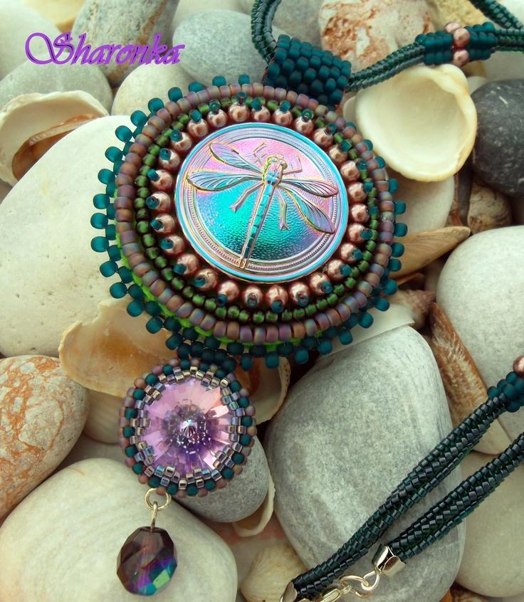 Vážkový fialkový Výšivka na filcu, obšitý vážkový knoflík, použité voskované perličky a japonský rokajl toho a miyuki, doplněný rivoli Swarovski v barvě vitrail light a fialovou ohňovkou. Knoflík je zavěšený na spirále šité stehem herringbone japonským rokajlem miyuki. Velikost přívěsku je 6 cm, celková délka je 11 cm. Délka spirály je 45 cm.