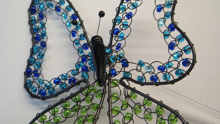 Křídla+motýlí...+Dekorativní+zápich+do+květin+nebo+vázy.+Zápich+je+tvořen+skleněným+tělem+motýla+černé+barvě+a+skleněnou+tyčkou+k+zápichu+v+čiré+barvě.+Motýlí+křídla+jsou+z+černého+žíhaného+drátu,+zdobeného+jemnými+skleněnými+korálky+v+zelené,+světle+a+tmavě+modré+barvě.+Výška+celého+zápichu+je+cca+23+cm,+rozpětí+křídel+je+cca+9,5+cm.+Ve+vlhkém...