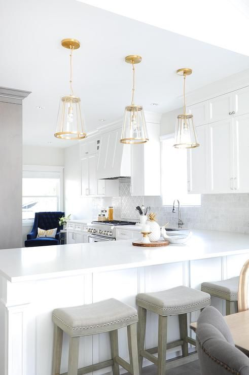 Gorgeous l-shaped white kitchen is illuminated by three glass and brass lanterns hung above a white peninsula topped with a white quartz countertop seating gray and wood fabric barstools.