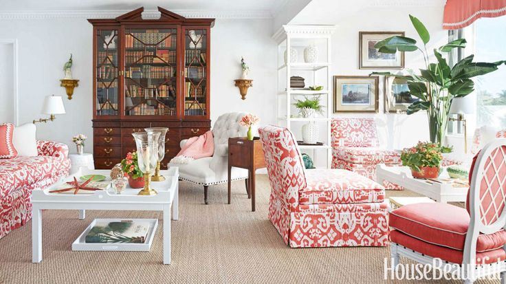 A vintage breakfront, filled with books that belonged to Gilman's father, adds character and tradition to the airy, light-filled living room. White tufted armchair by Thibaut Fine Furniture. Donovan designed the white-painted étagère to divide the two seating areas. Walls are sheathed in Thibaut's Tahitian Weave grass cloth for luxurious texture. Trays under twin coffee tables from Oomph catch stray books, newspapers, and magazines. Floor lamps, Circa Lighting.