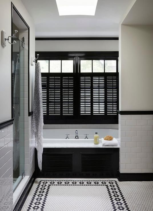 Chic black and white bathroom features a window covered in black shutters complementing black molding and framed by a white wall positioned above a marble deck black shuttered drop in tub finished with a polished nickel tub filler and a white subway tile backsplash.