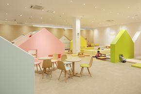« Mama Smile » est une garderie et une aire de jeux implantées dans un centre commercial au Japon. Bien que situé à l'intérieur du centre commercial, cet espace donne un sentiment de sécurité comme être dans une maison confortable.  L'entrée de l'aire de jeux a une ouverture découpée dans un mur blanc, telle la forme d'une maison dessinée par un enfant. Derrière l'ouverture, on retrouve un monde coloré, avec des maisons en 7 couleurs dans les tons de jaune, rose, vert et bleu.