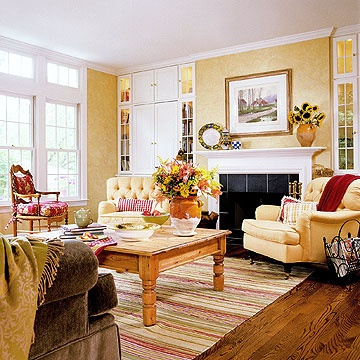 Sunny Living  This color palette warms in any season. Walls in pale gold bring out the wood tones in the flooring. Against this buttery backdrop, we notice accents of red in one chair, several pillows, and an area rug.Living Rooms, Area Rugs, Home Decorating, Decorating Ideas, Crown Moldings, Colors Palettes, Red And Yellow Living Room, Yellow Chairs, Crowns Moldings