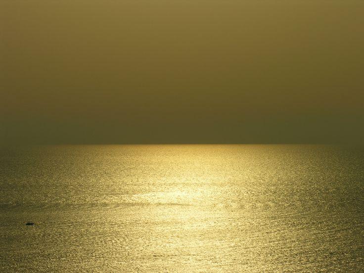 Una barchetta solitaria solca il mare color oro - Forio d'Ischia