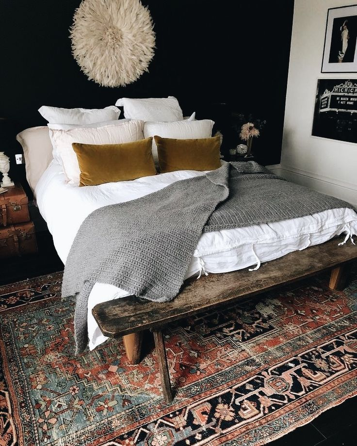 Forget the art over bed, dark wall, white linens, velvet pillows (texture not print) nubby throw, scarred old wooden bench, worn Asian rug in soft colors