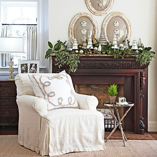 A garland doesn't have to drape in order to be a garland. Here, a variety of greens comes together in mounds and clumps, supplying movement to the mantel. Antique and vintage mercury-glass balls and new mercury-glass Christmas trees add sparkling contrast. /