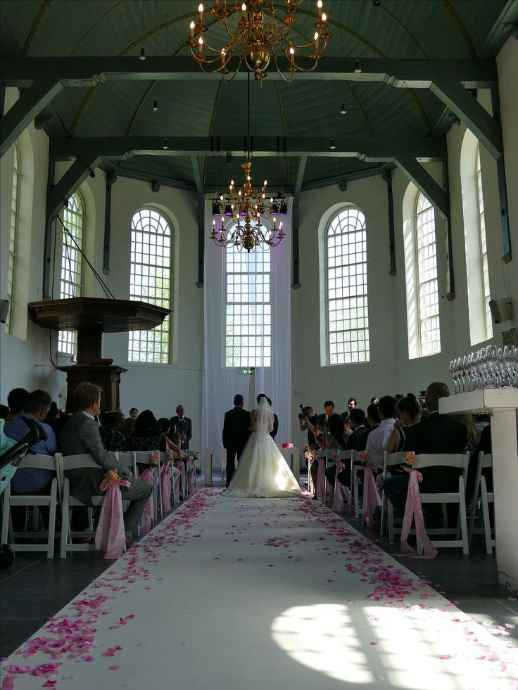 Sprookjes bruiloft met roze bloemblaadjes. Het is prachtig in de Buiksloterkerk.