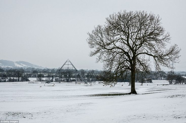 It comes after deadly black ice, floods and fog were said to bring fresh chaos to Britain today, adding to the devastating effects of recent extreme weather. Pictured:Snow surrounds the skeleton structure of the Pyramid Stage at the site of the Glastonbury Festival site at Worthy Farm today