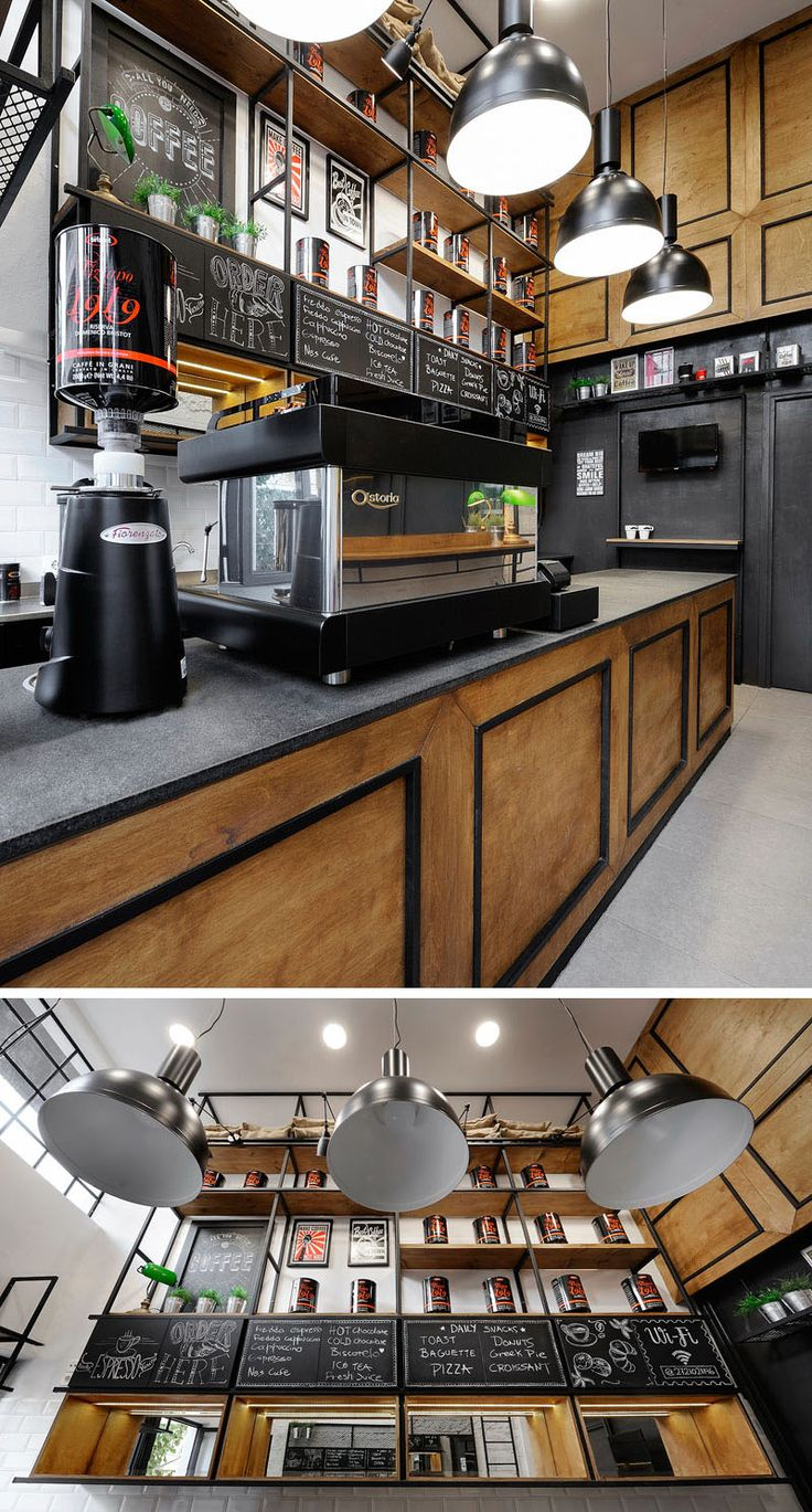 The service area of this modern coffee shop features a wood counter with dark countertop, while behind it, metal and wood shelves reach all the way to the ceiling.