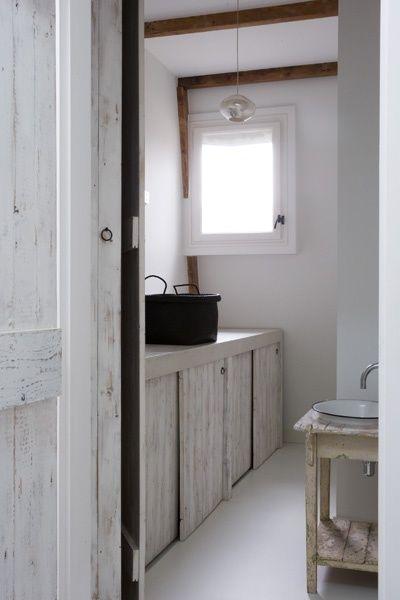 opgeruimde wasruimte met white wash houten deuren