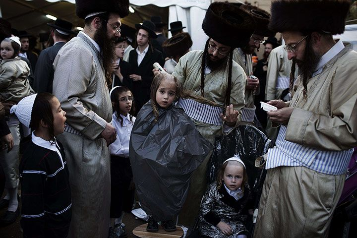 And here's a three-year old Jewish boy having his first haircut from his Ultra Orthodox father during during the celebration at the grave site of Rabbi Shimon Bar Yochai