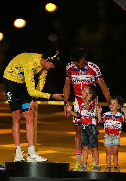 Winner of the 2013 Tour de France, Chris Froome of Great Britain and SKY Procycling shares a joke with the children of third placed Joaquin 'Purito' Rodriguez