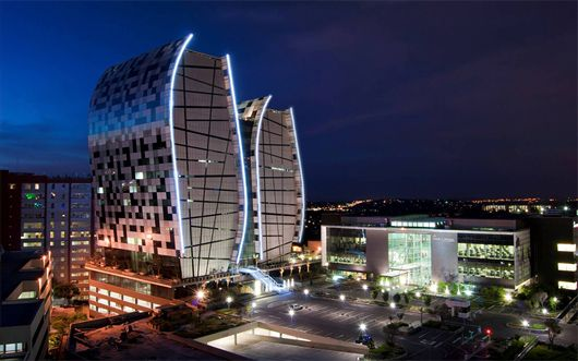 """Paragon Architects in Johannesburg, South Africa, have dramatically changed the skyline of the Sandton section of town with the new 15 Alice Lane Towers. The 17-story (hard to believe it's not taller) corporate offices for a major law firm is incredibly striking with its curved facades and its neon-lit silhouette in the dark."""