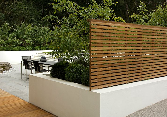 White rendered wall, horizontal slatted fence in contemporary garden