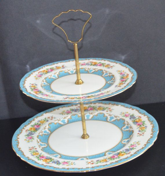 A double tier Lyric Crown Staffordshire Cake stand or Tidbit tray in blue tunis. Both marked on the bottom circa 1950s. Pretty decoration, perfect for parties and weddings. Measures: 8 bottom plate, 7 1/2 top plate, 10 tall overall Condition no chips, top plate has spider