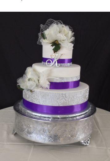 Purple and diamond ribbon wedding cake with silk magnolia flowers