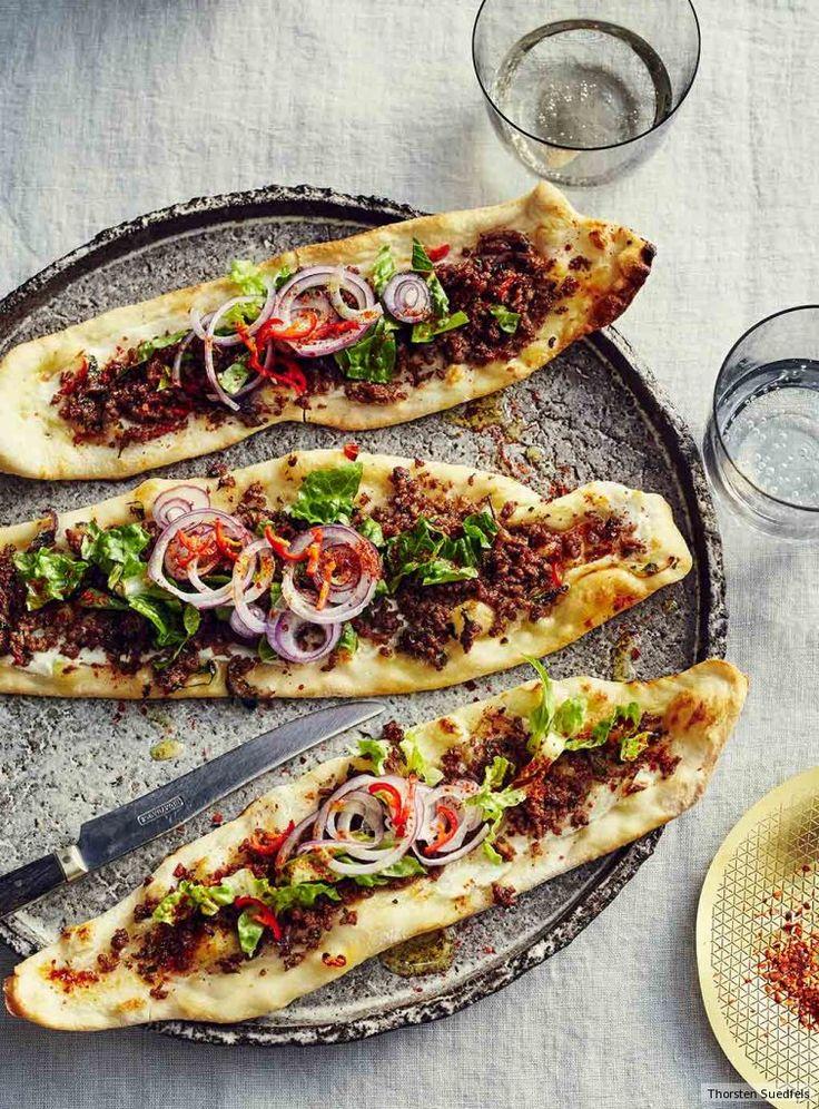 Pizza wie nie: Die Hefefladen werden fünf Minuten gebacken und dann mit gebratenem Lammhack, Chili, Salat und roten Zwiebeln belegt. Am besten gleich vom Blech weg verputzen.