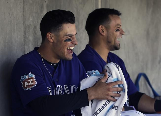 All-star third baseman Nolan Arenado, left, wants the Rockies to have a lot to smile about this season.
