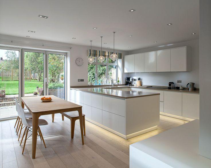 Cocina - comedor con isla. En blanco y con iluminación ambiente bajo muebles.